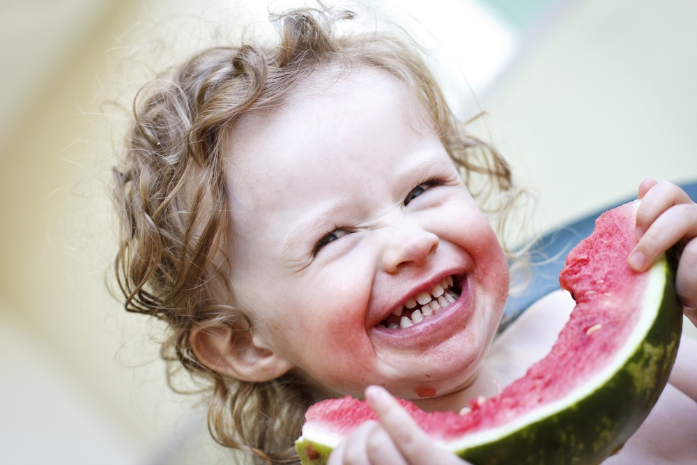 A Little Girl Finishing a Slice of Watermelon